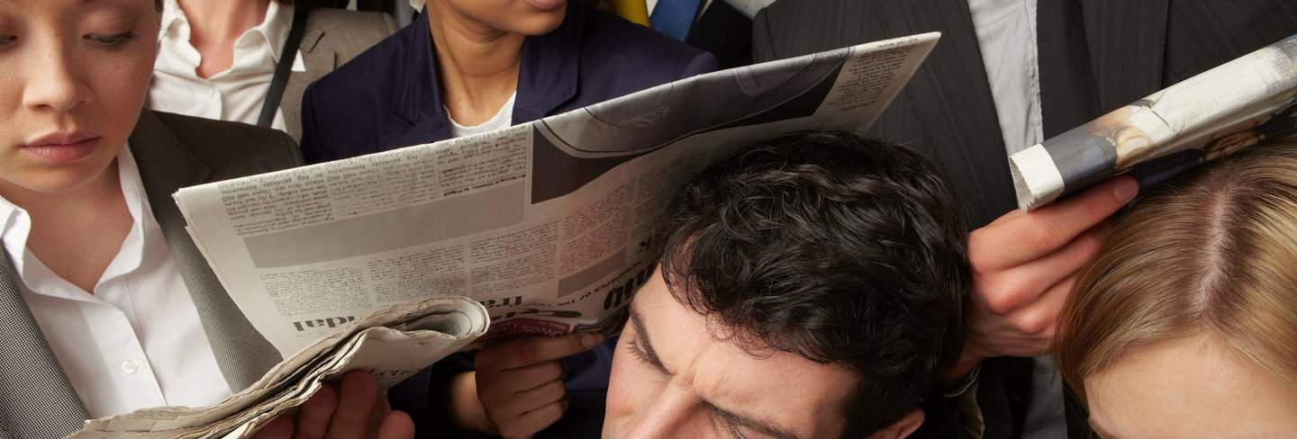 People on the train reading newspapers