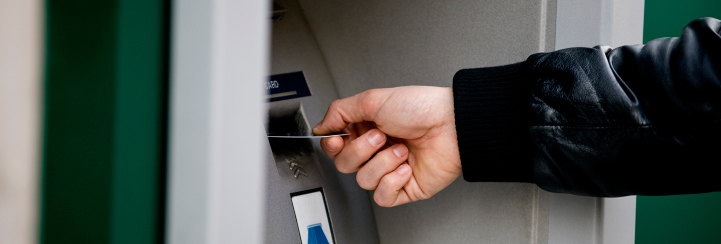 Male hand using cashpoint