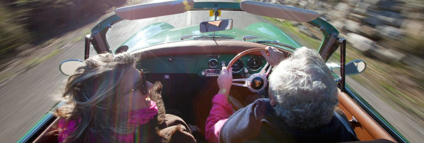 retired couple driving convertable