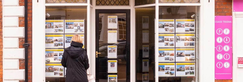 woman looking in estate agent window