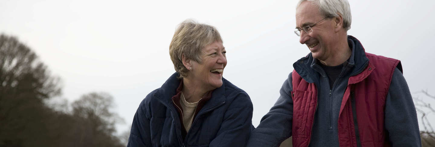 Old couple laughing outside