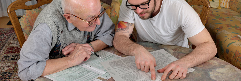Old and young man looking at bills